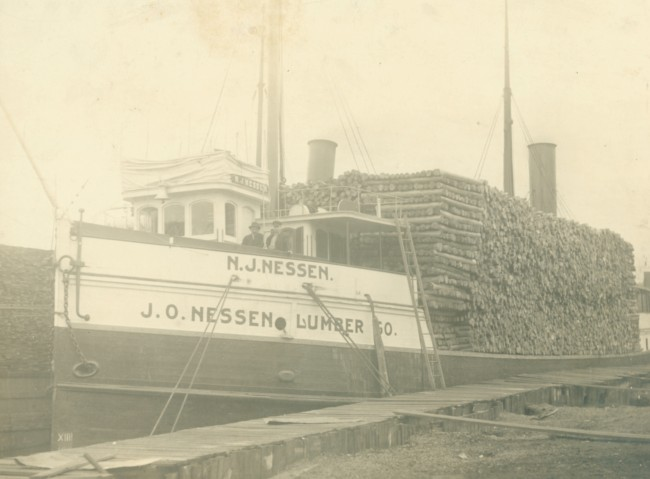 Historical photo of a fully loaded lumber ship from the N.O. Nessen Lumber Company