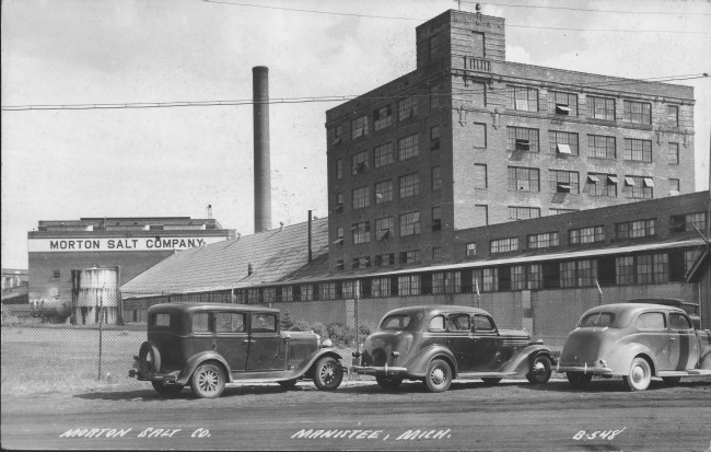 Historical photo of the Morton Salt Company factory in Manistee Michigan cars are parked in front of the large brick building with the iconic smokestack in the background