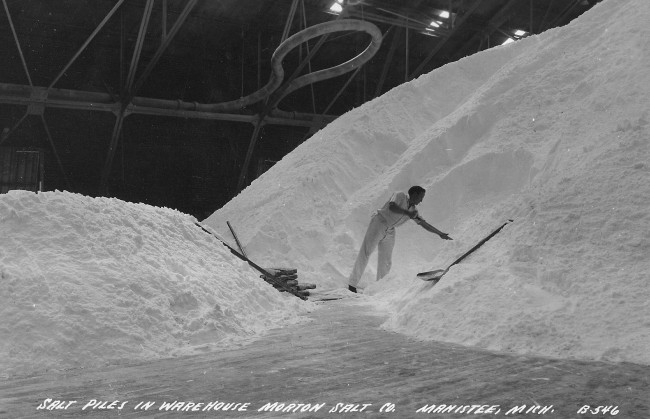 A worker is seen shoveling salt that is piled to the ceiling in a warehouse at the Morton Salt Company plan in  Manistee Michigan