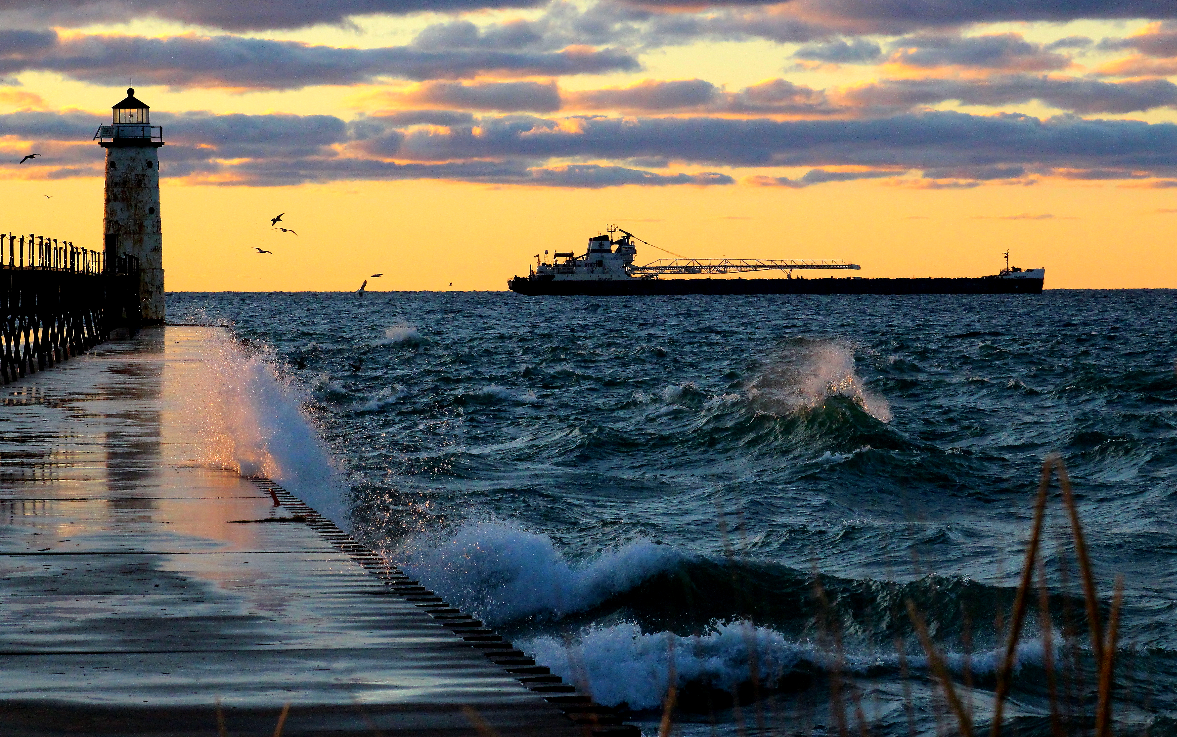 Freighter seen exiting the harbor with waves washing over Fifth Avenue pier as the sun is setting