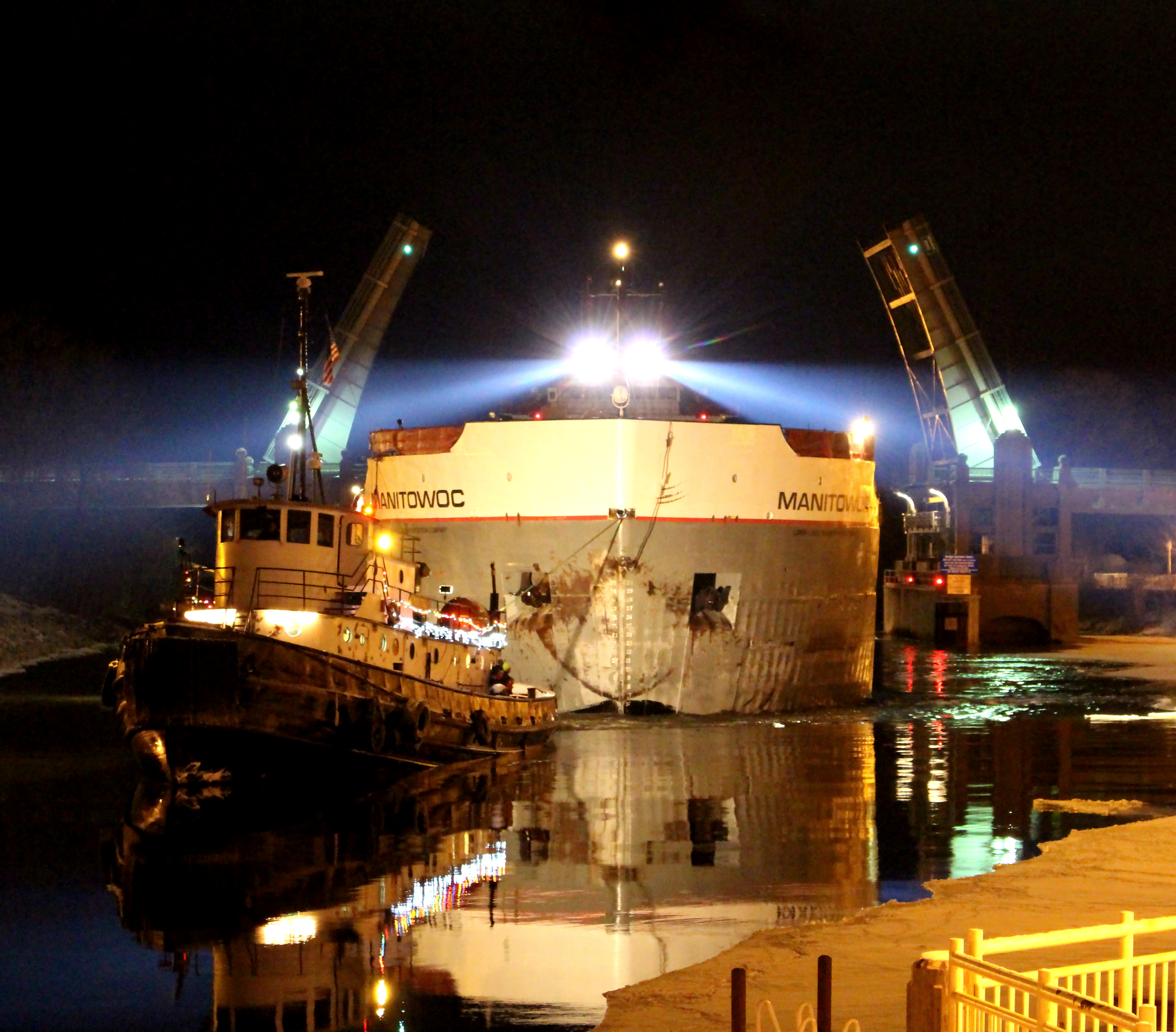 Tug Boat pulling Freighter Manitowoc through the US 31 Bridge at night