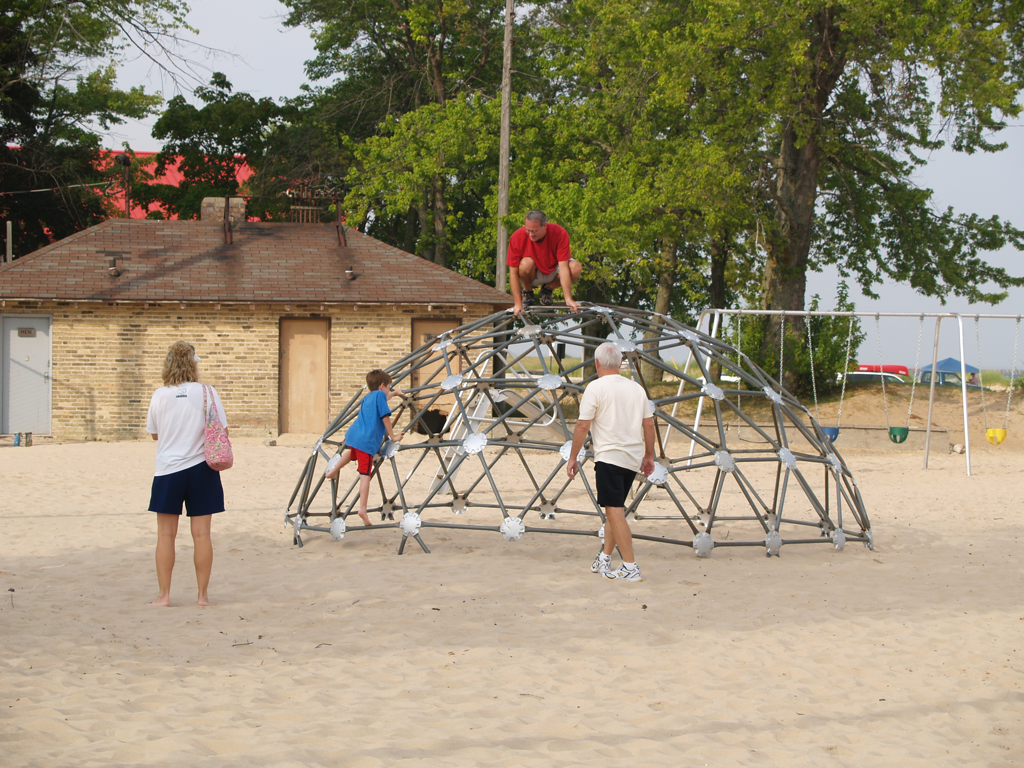 People are playing on the large climbing sphere at Fifth Avenue Beach