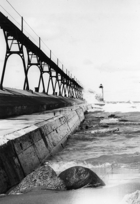 Historical photo of the catwalk and Lighthouse at Fifth Avenue Beach with waves washing up against the shore
