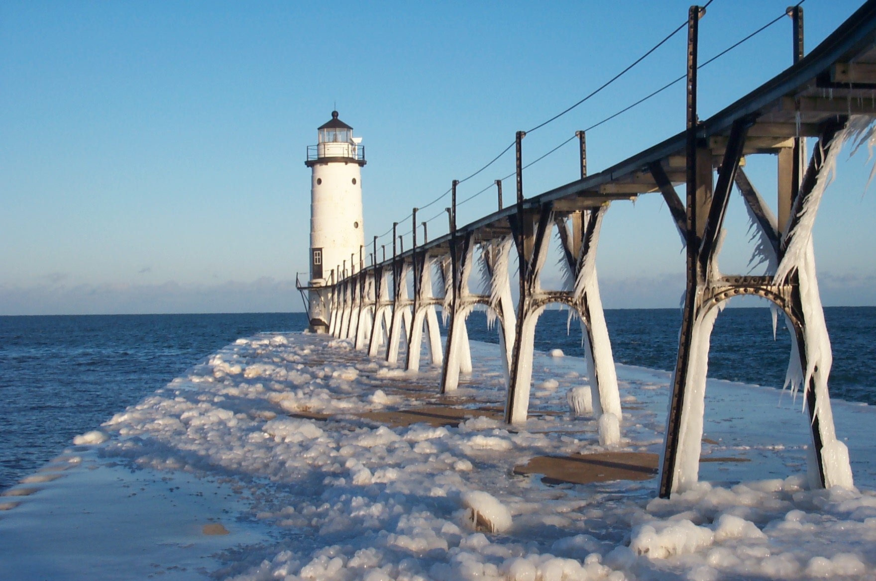 Sunny winter day with ice and snow on the pier and catwalk leading up to the lighthouse at Fifth Avenue