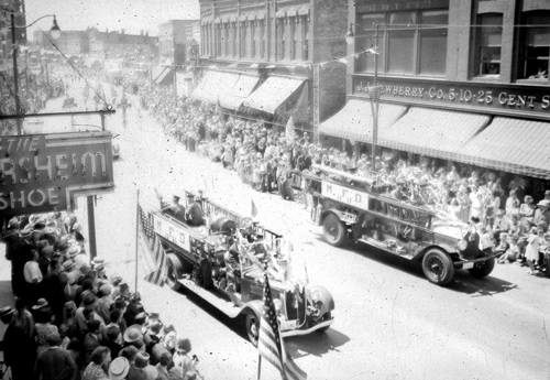Two fire trucks are the focal point of the spectators who were in attendance for this parade that took place on River Street  in downtown Manistee in this undated photograph