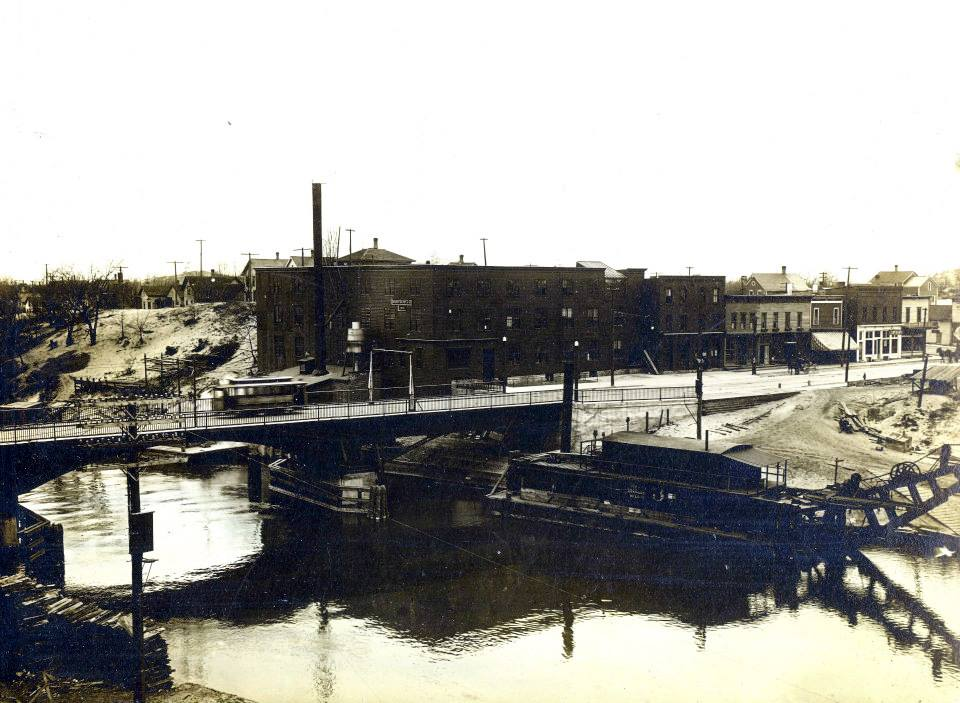 Historical Photo of Manistee Manufacturing Co located on the Manistee River Channel with the old Maple Street Bridge