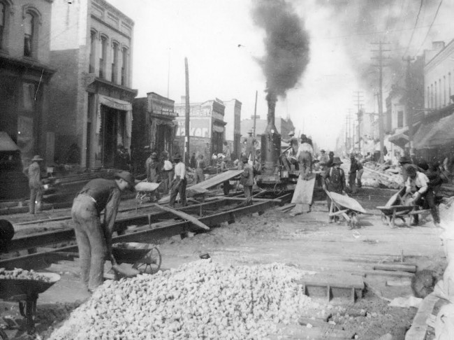 Historical Photo of the paving River St early 1900 workers with wheelbarrows are seen working along with heavy equipment of the era