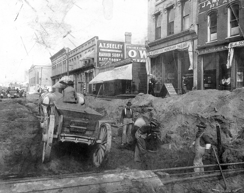 Early photo of River Street  where men are working on the street with a wagon