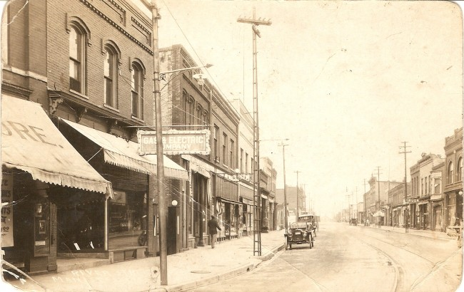 Undated historical photo of downtown Manistee with cars parked on the street, awnings handing over the sidewalk and old fashioned metal electrical poles.
