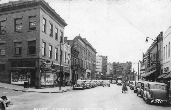 River Street as seen in 1940 with vehicle parked on both sides of the street and pedestrians crossing the street