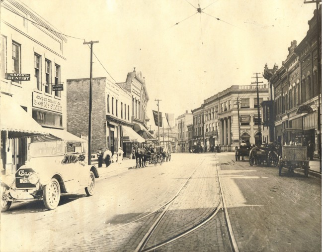 Both cars and horses are seen on both sides of the street with the trolley tracks in the  middle as you look east on River Street in downtown Manistee towards the Manistee County Bank in this historical photo