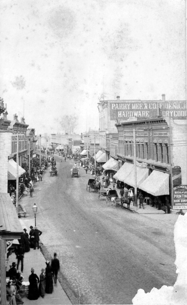 Old photo of River Street taken from a rooftop that over looks the activity on the street with people shopping, horses and carts are seen along the street as canvas awnings hang over the sidewalk