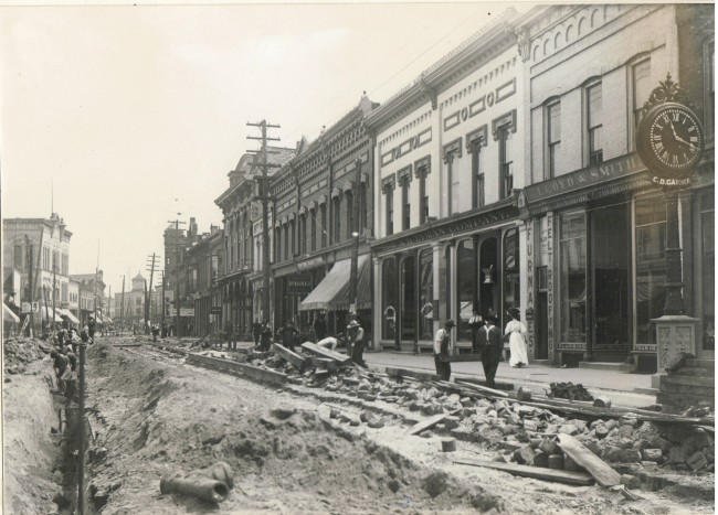 Historical photo of street construction on River Street in front of the A.H. Lyman building as shoppers walk past the workers