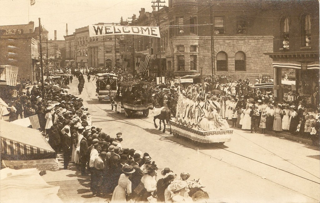 The streets of River Street in downtown Manistee are lined with spectators who watch floats that are being pulled by horses during this summer parade in an undated photo