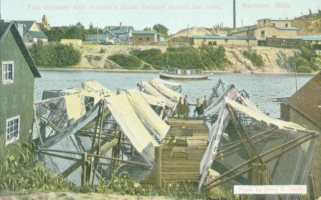 Photos of net shed and nets on the Manistee River Channel with men working on the dock with a boat and manufacturing buildings in the background