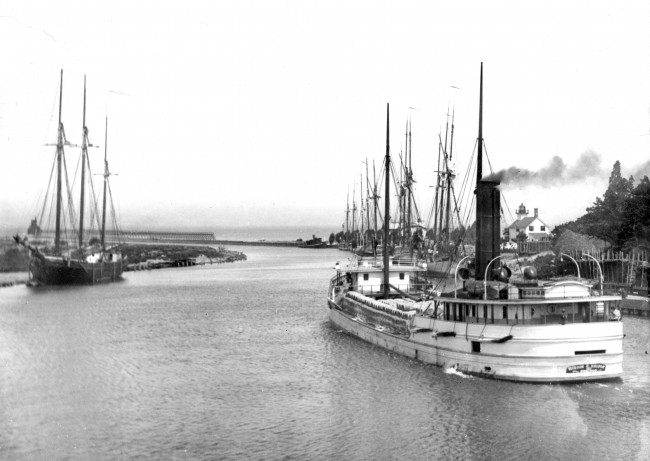 Undated historical photos of a wooden sail boat entering Manistee Harbor and a steam boat exiting harbor with the lighthouse in the background