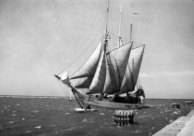 Historical photo of the JT Wing sail boat in full sail on a windy day between the pier heads in Manistee Michigan