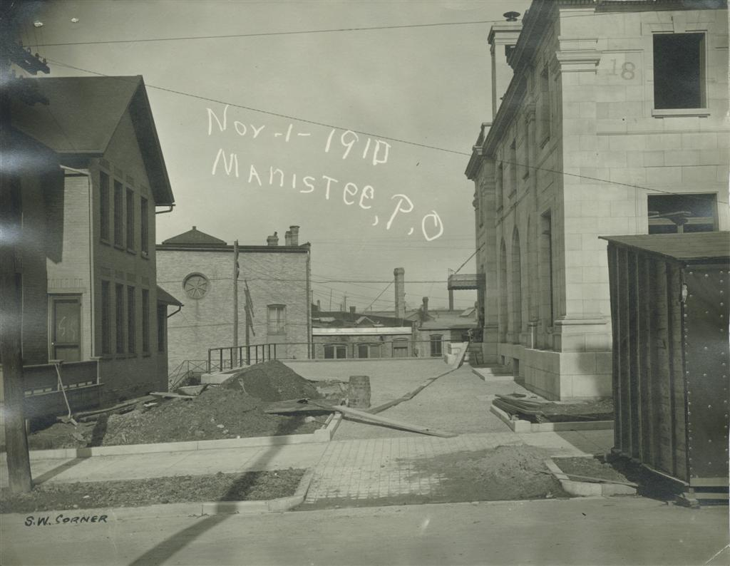 Historical photo taken November 1910 showing the drive on the west side of the building, railing is in place where rings will be installed for tying up the horses