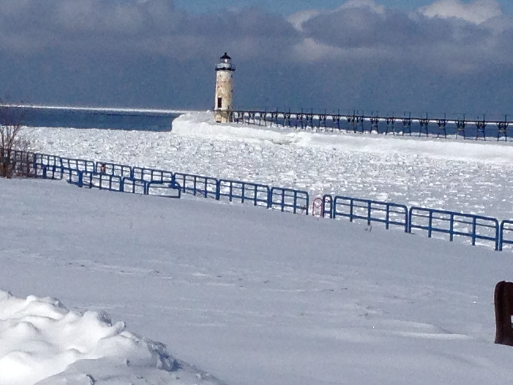 Winter scene of Manistee Harbor frozen over as seen from First Street with Fifth Avenue Lighthouse