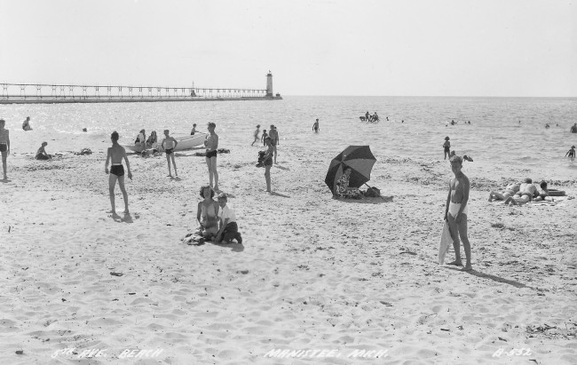 Undated photograph of people enjoying a beautiful summer day at Fifth Avenue beach with the lighthouse in the background