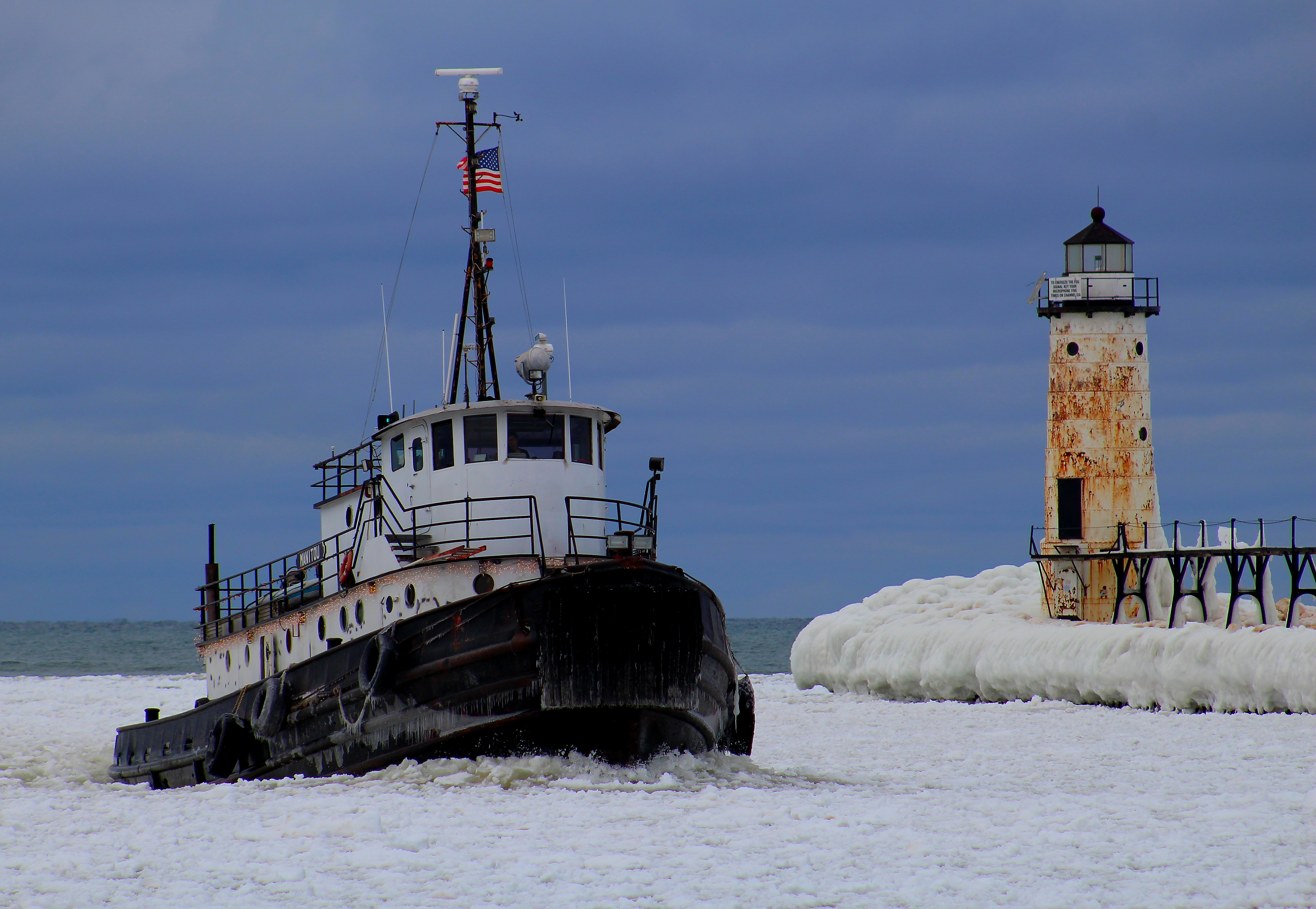 Tugboat entering Manistee River Channel with Fifth Avenue Lighthouse in background in winter