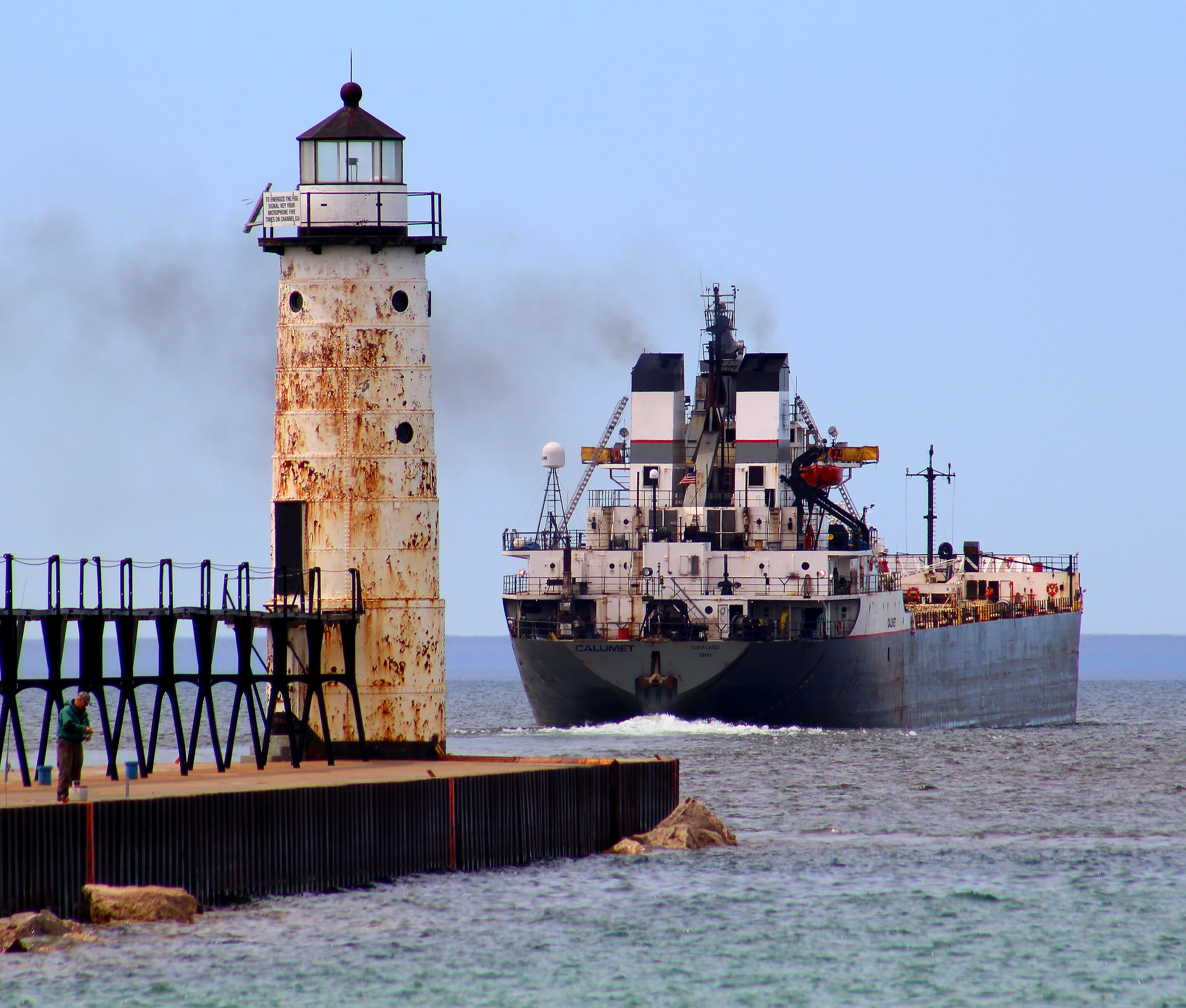 Freighter exiting harbor next to Lighthouse at Fifth Avenue