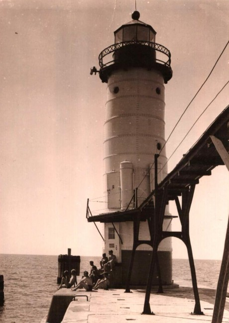 Historical Photo of the Fifth Avenue Lighthouse showing the catwalk and people sitting around the steps to the lighthouse taken around 1940