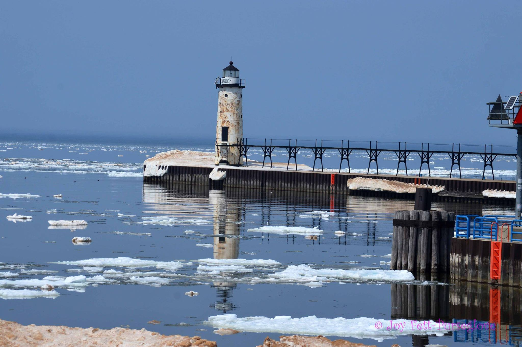 Fifth Avenue Lighthouse with ice floating in the Manistee River Chanel as seen looking over the harbor from First Street Beach